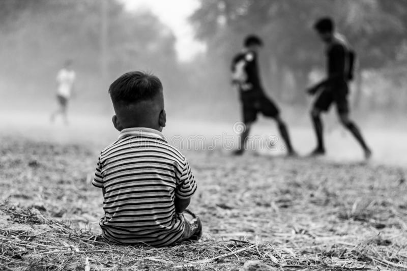 Young boy sitted wathing street soccer game stock photos
