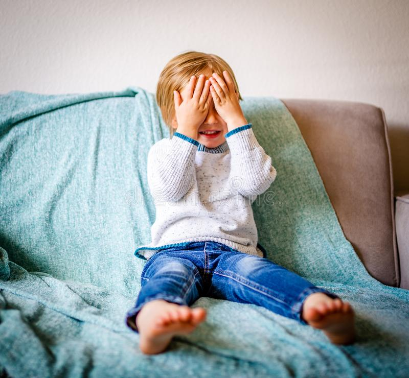 Young Boy Sitting on Couch Crying stock photo