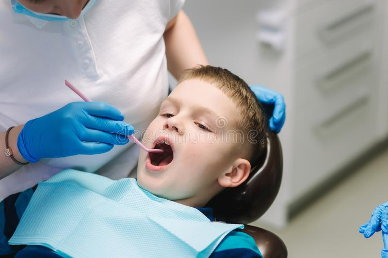 Young boy sitting on the dental chair at the office. Children`s dentist examination baby teeth.  royalty free stock image