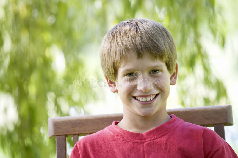 Young boy sitting in a garden chair, close-up stock images