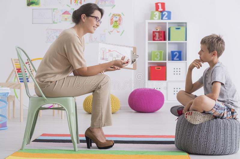 Room with colored carpet. Young boy is sitting on a grey pouf in front of his psychotherapist in a room with colored carpet stock photos