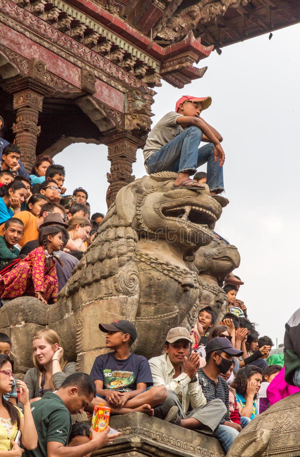 Young boy sitting on lion sculpture. To get a better view of the chariot being pulled through the streets of Bhaktapur during the annual Bisket Jatra festival royalty free stock photography