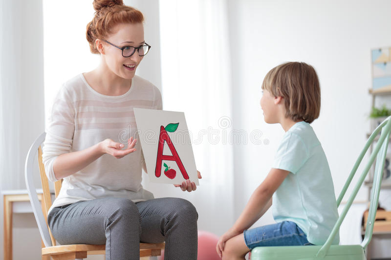 Friendly speech therapist and boy. Young boy sitting on mint chair focusing on speech lessons with friendly speech therapist stock photo