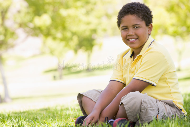 Download Young boy sitting outdoors stock photo. Image of emotion - 5944354