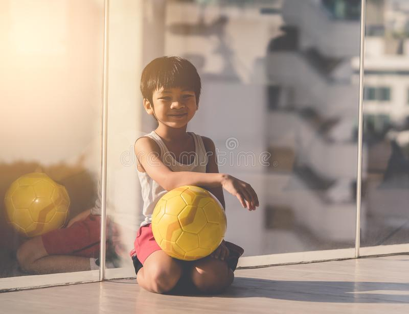 Young boy sitting with soccer on the floor royalty free stock images