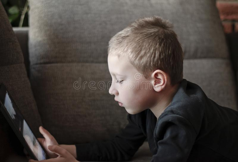 Young boy sitting on sofa in living room and watching cartoons on tablet. Portrait of a smart pre-school child using devices at. Home. Modern kid and education stock photography