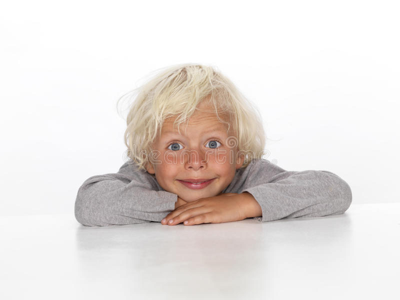 Young boy sitting at a table. Cute, young, blonde-haired boy sitting at a table royalty free stock photos