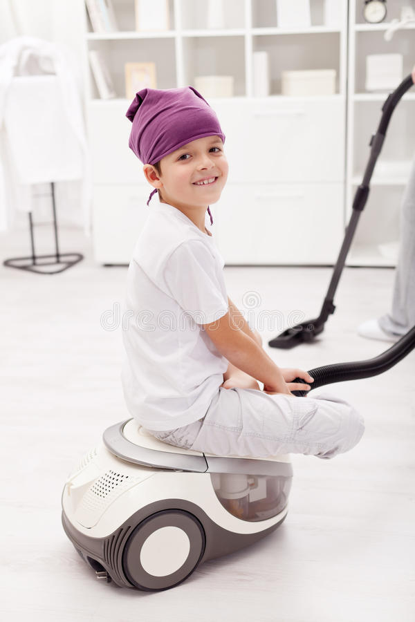 Young boy sitting on vacuum cleaner stock photo