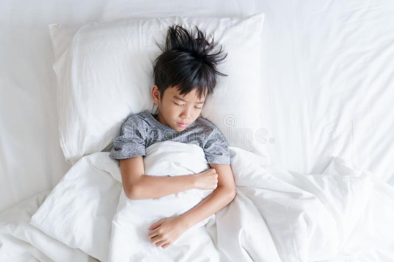 Young boy sleep on a white bed stock image