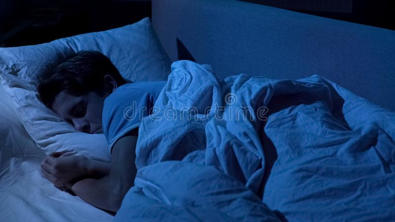 Young boy sleeping after hard day, cozy comfortable bed and soft pillows, relax stock photography