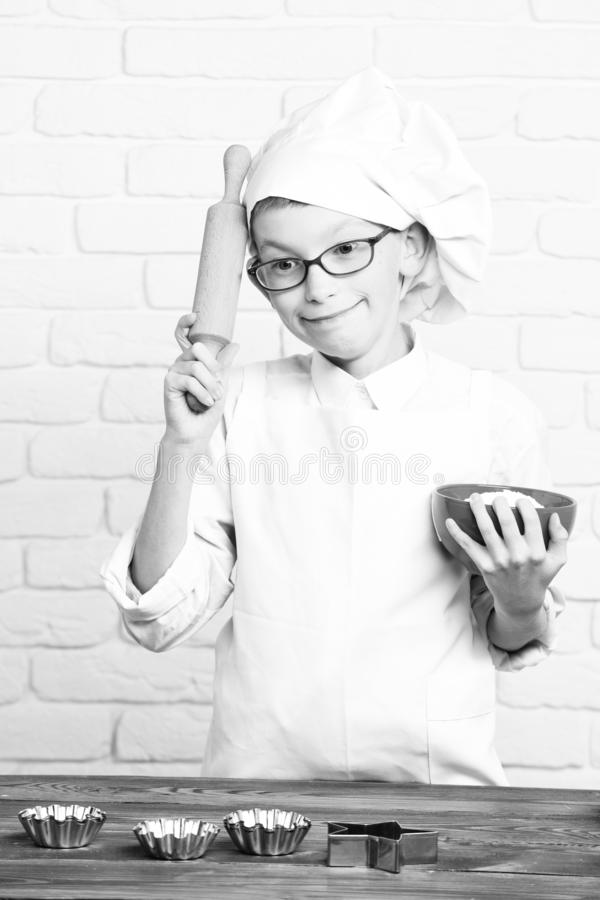 Young boy small cute cook chef in white uniform and hat on funny face with glasses standing near table with molds for stock images
