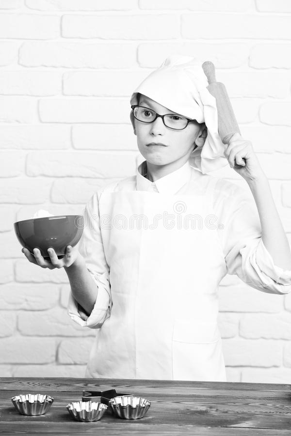 Young boy small cute cook chef in white uniform and hat on serious face with glasses standing near table with molds for. Cakes and holding red bowl with rolling royalty free stock photography