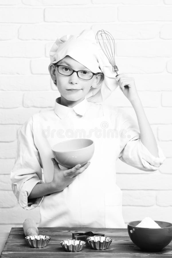Young boy small cute cook chef in white uniform and hat on serious face with glasses standing near table with rolling. Pin molds for cakes and holding turquoise royalty free stock image
