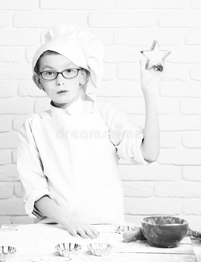 Young boy small cute cook chef in white uniform and hat on stained face flour with glasses standing near table with. Rolling pin red bowl and holding cookie stock photo