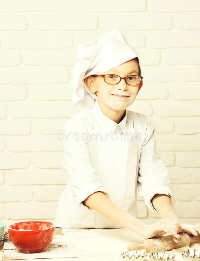 Young boy small cute cook chef in white uniform and hat on stained face flour with glasses standing near table with. Rolling pin red bowl and cooking on brick stock photo