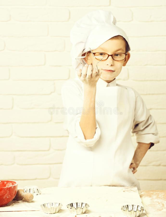 Young boy small cute cook chef in white uniform and hat on stained face flour with glasses standing near table with. Rolling pin red bowl and holding cookie royalty free stock photo