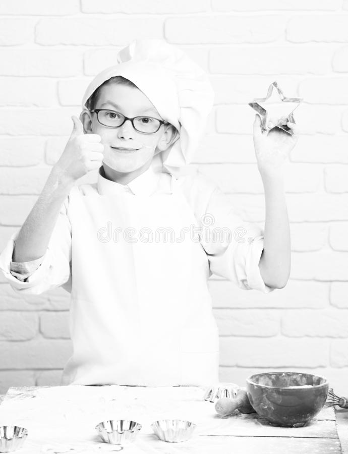 Young boy small cute cook chef in white uniform and hat on stained face flour with glasses standing near table with royalty free stock photography