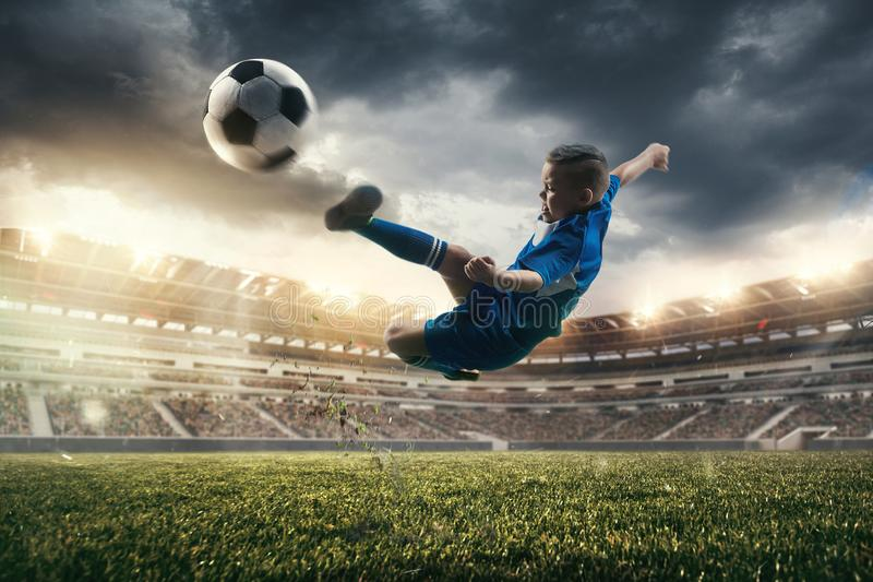 Young boy with soccer ball doing flying kick at stadium stock photo