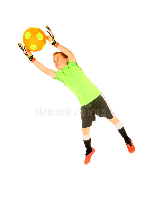 Young boy soccer goalie jumping to save from goal. Boy soccer goalie jumping to save goal catching the soccer ball white studio background royalty free stock photos