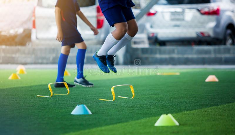 Young boy soccer player Jogging and jump between marker and yellow hurdles. Soccer training stock images