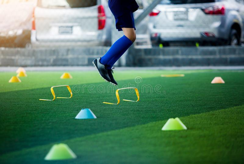 Young boy soccer player Jogging and jump between marker and yellow hurdles. Soccer training stock photos