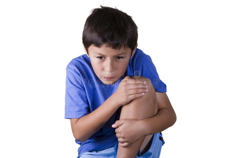 Young boy with sore knee. Young boy holding his sore knee - on white background stock photo