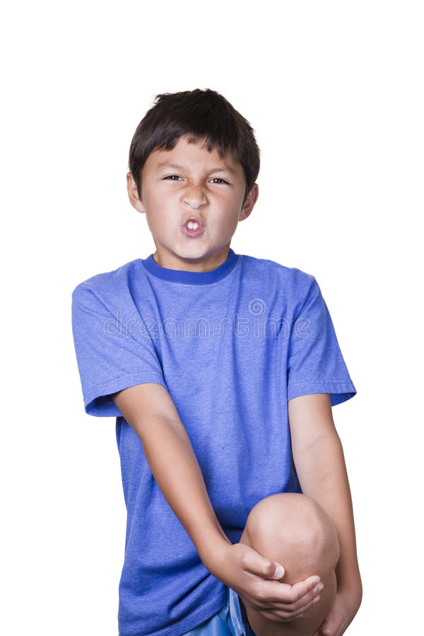 Young boy with sore leg. Young boy holding his sore leg - on white background stock image