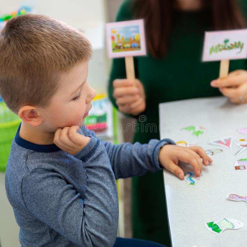 Young boy in speech therapy office. Preschooler exercising correct pronunciation with speech therapist. Child Occupational Therapy royalty free stock photos