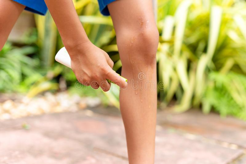 Young boy spraying insect repellent against mosquitos bites on his legs in the garden. royalty free stock photography