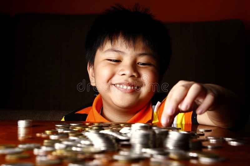 Young Boy Stacking or Piling Coins royalty free stock photography