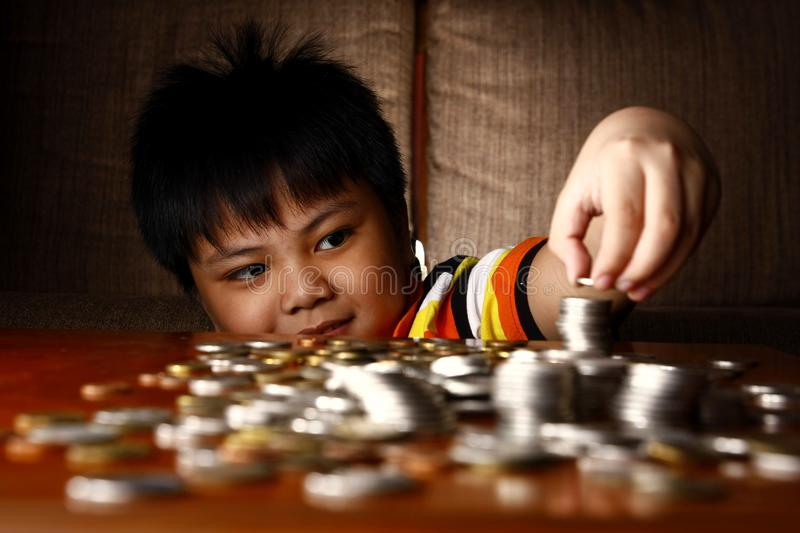 Young Boy Stacking or Piling Coins royalty free stock photos