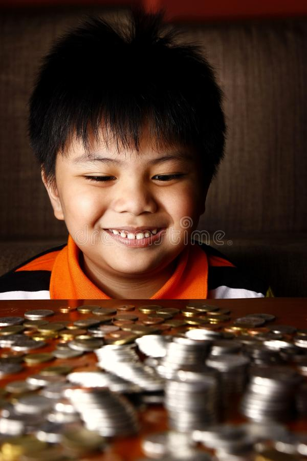 Young Boy Stacking or Piling Coins stock images