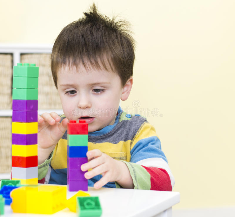 Young boy stacks connecting blocks royalty free stock image