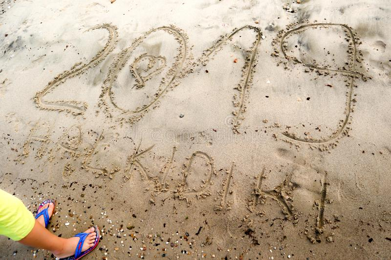 Young boy standing in front of number 2019 written on the sea sand with drawn heart in number 0 and text Halkidiki. Natural sand textured background. New year stock photos
