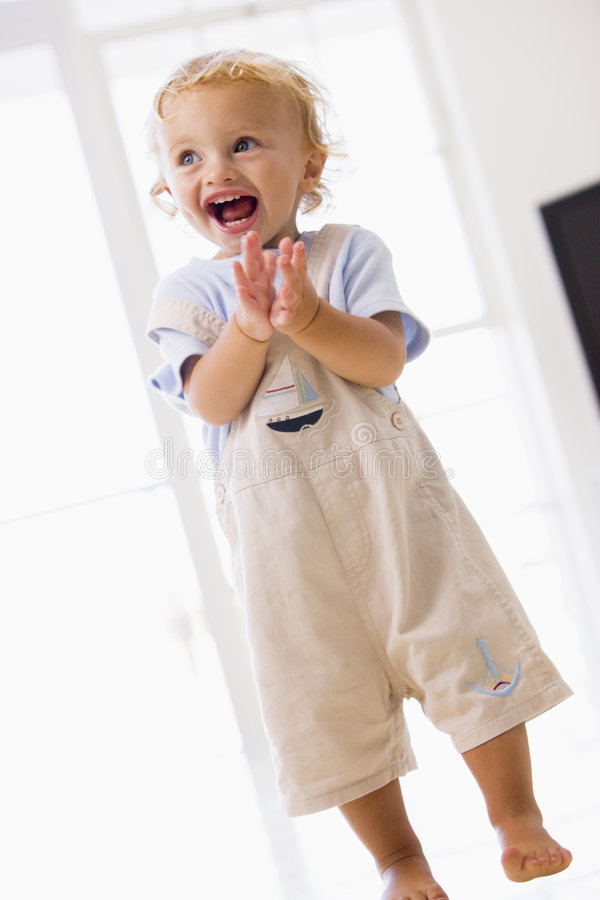 Download Young Boy Standing Indoors Applauding And Smiling Stock Image - Image: 5639899