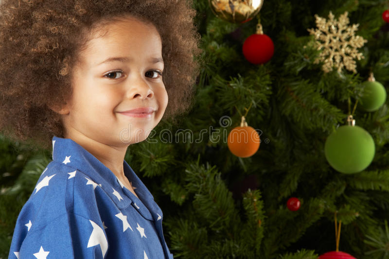 Young Boy Standing Next To Christmas Tree stock photography