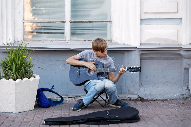 Young boy street musician playing acoustic guitar on the street stock photography