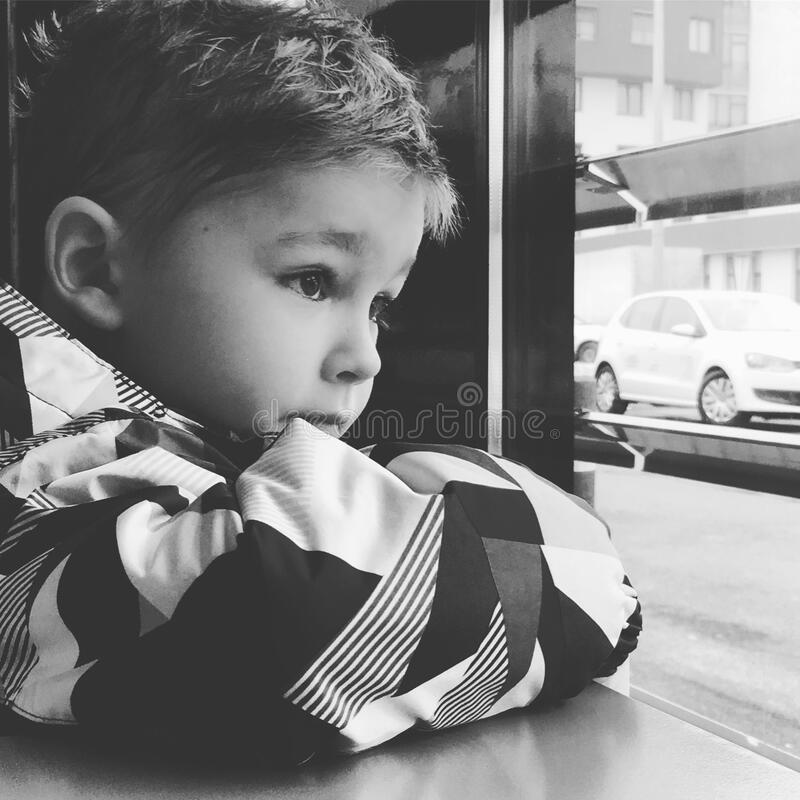 Young Boy Looking Out A Window. A young boy stuck indoors, because of the Coronavirus outbreak, looks out a window during springtime stock photo