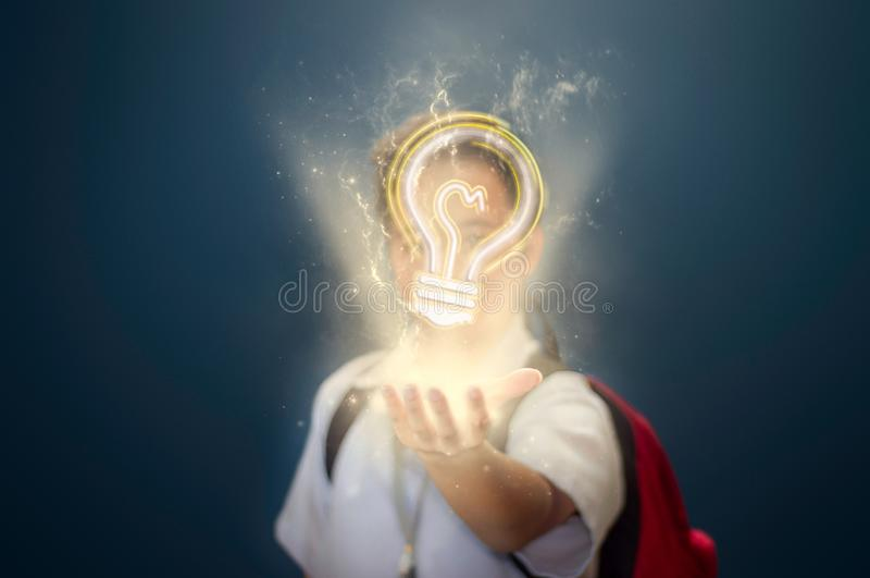 Young Boy Student With Floating Light Bulb Above His Hand To Represent An Idea stock image