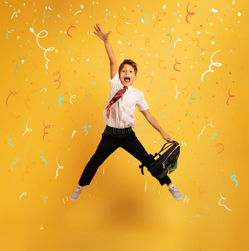 Young boy student jumps high happy for the promotion. Yellow background. Young boy student jumps high happy for the promotion with honors. Yellow background royalty free stock photos
