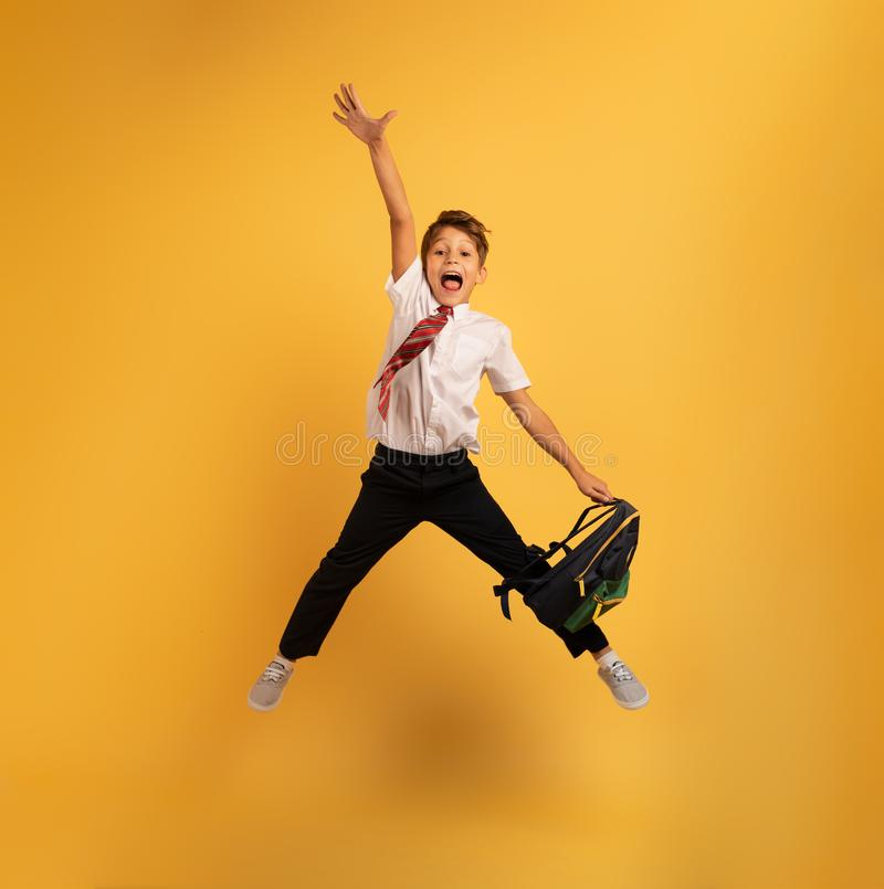 Young boy student jumps high happy for the promotion. Yellow background. Young boy student jumps high happy for the promotion with honors. Yellow background stock image