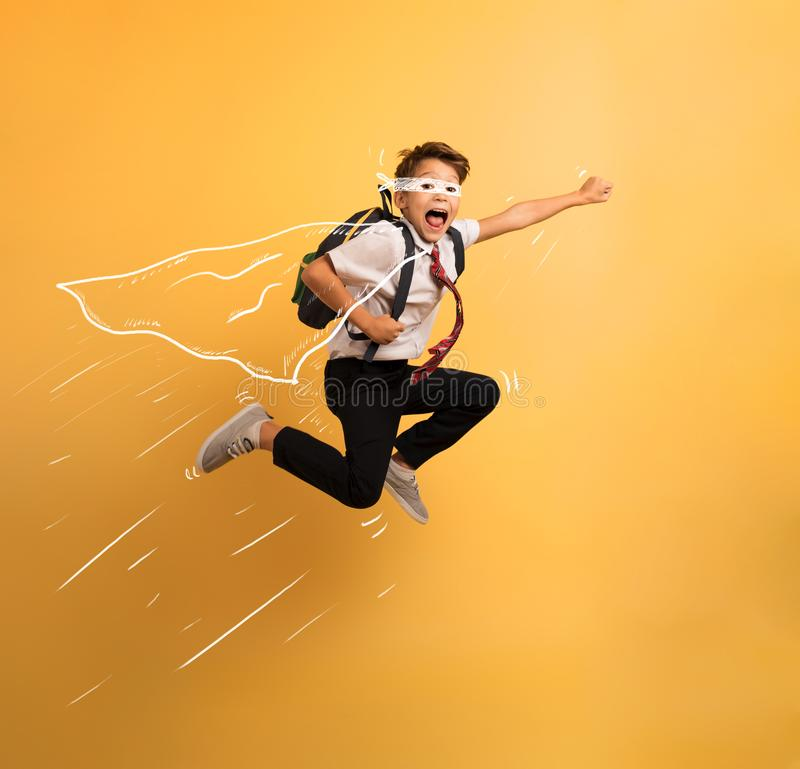 Young boy student jumps high like a super hero. Yellow background. Young boy student jumps high like a super hero to escape from school lesson. Yellow background stock photography