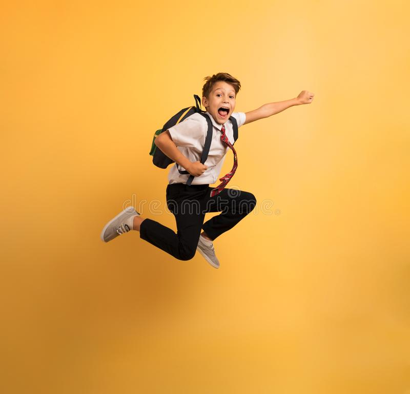 Young boy student jumps high like a super hero. Yellow background. Young boy student jumps high like a super hero to escape from school lesson. Yellow background royalty free stock image
