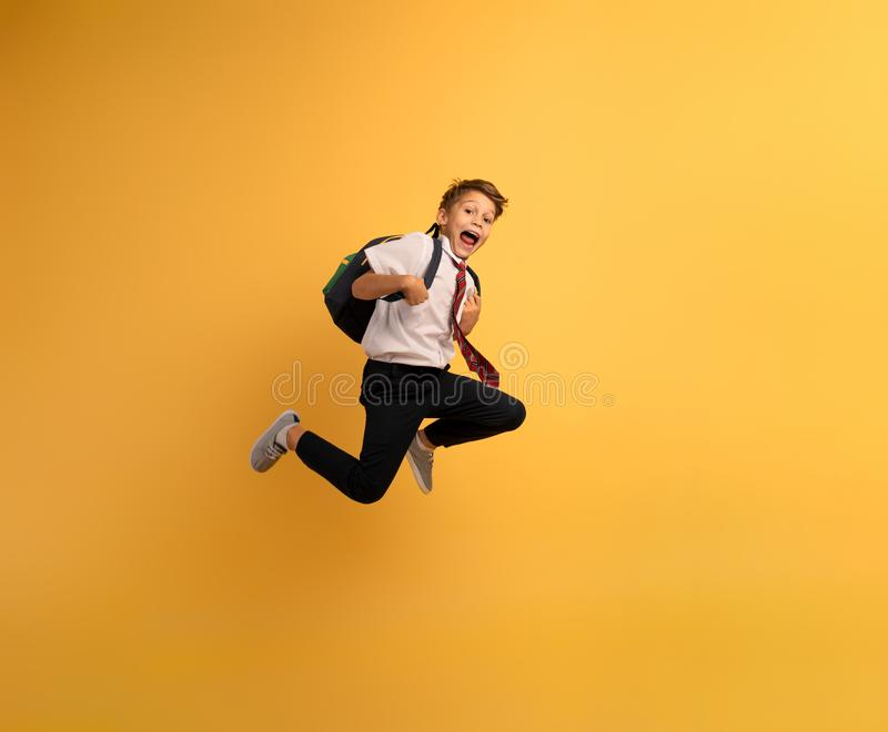 Young boy student runs fast to escape from school. Yellow background. Young boy student runs fast to escape from school lesson. Yellow background royalty free stock image