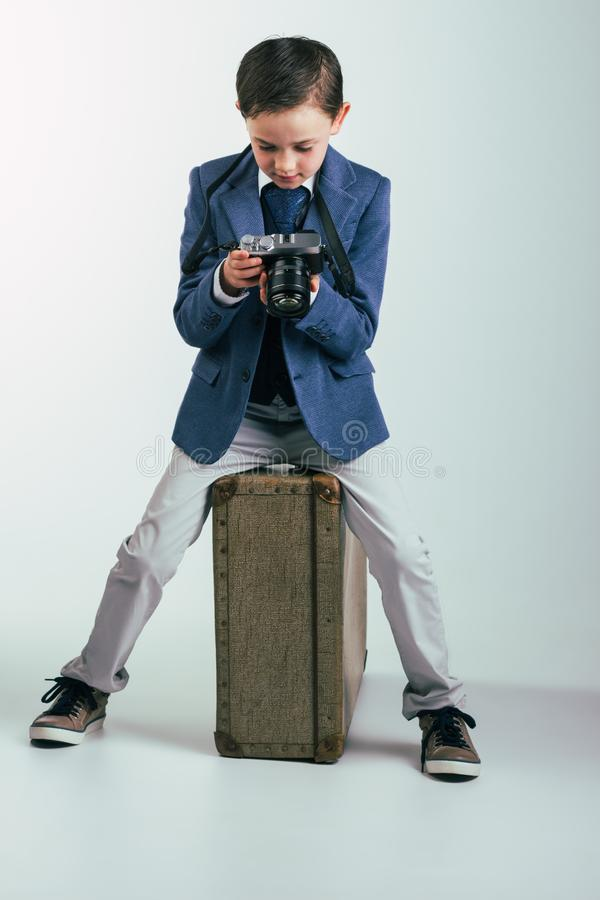 Young boy in suit with camera sitting on suitcase royalty free stock photography