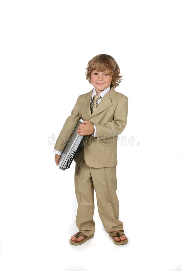 Young boy in suit with laptop stock photos