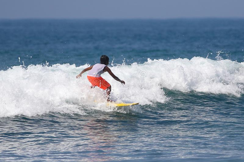 Young boy surfing on ocean waves in California stock photo