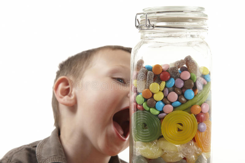 Young boy and sweet jar stock images