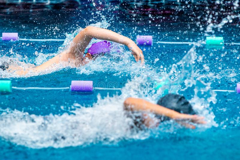 Young boy swimmers racing in freestyle royalty free stock photography