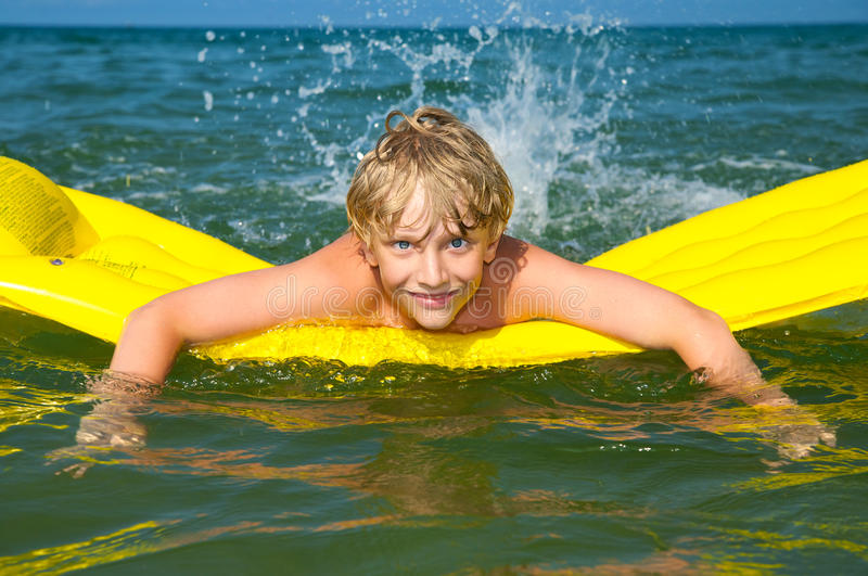 Young boy swimming on mattress in the sea stock photo